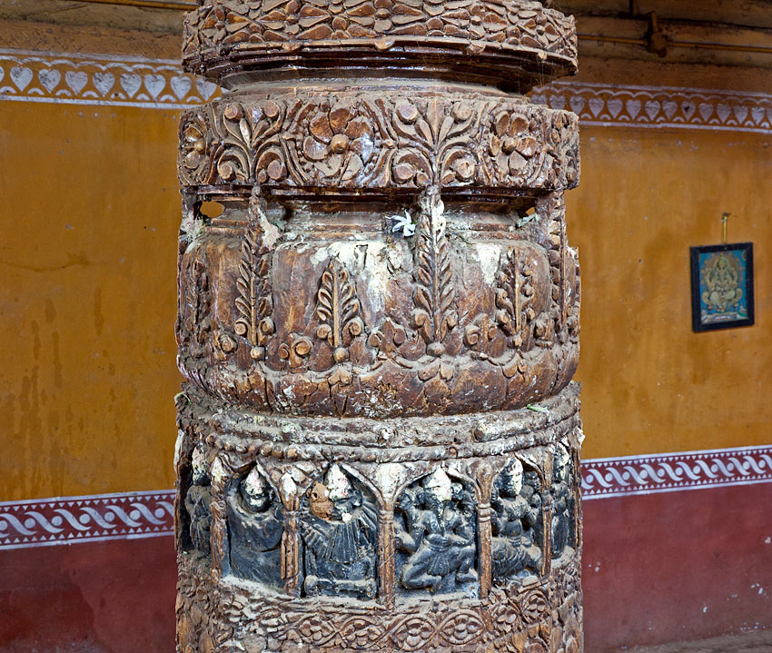 Intricately carved wooden pillars inside the temple