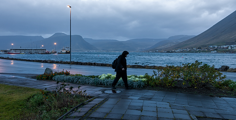 Lone walker on a stormy morning in Ísafjörður