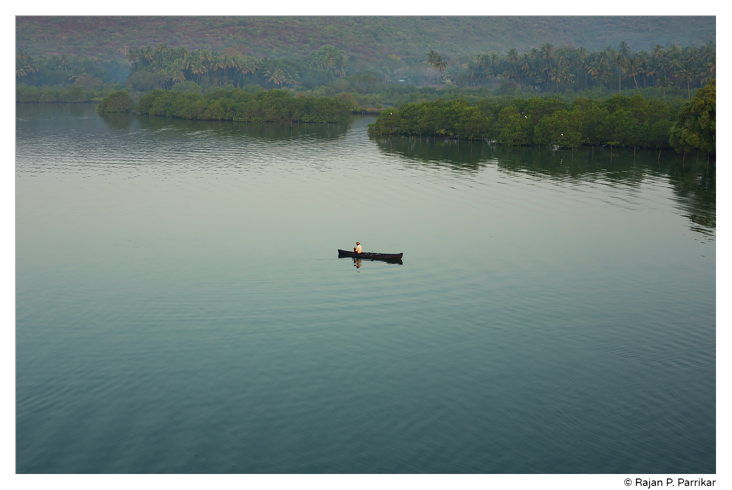 Lone fisherman on Chapora river in Siolim, Goa